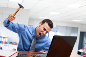 angry man with hammer about to smash laptop